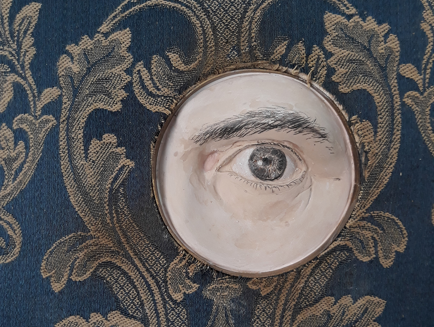 MR X's eye spy from a hole trought a brocade tapestry